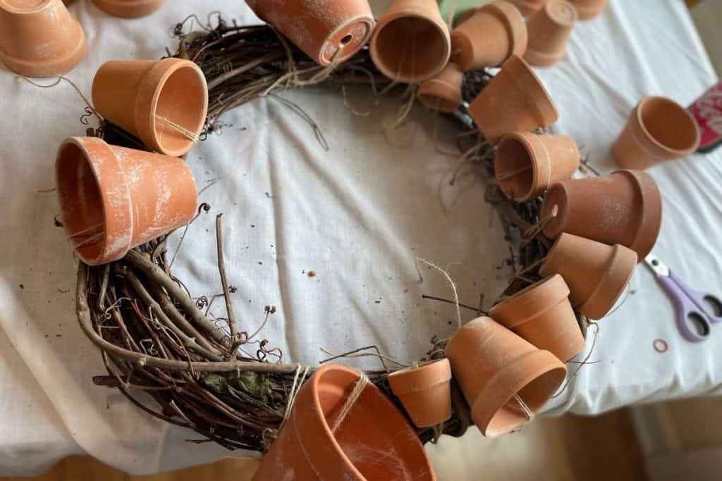 14 terracotta pots tied to a grapevine wreath for Fall DIY Wreath project