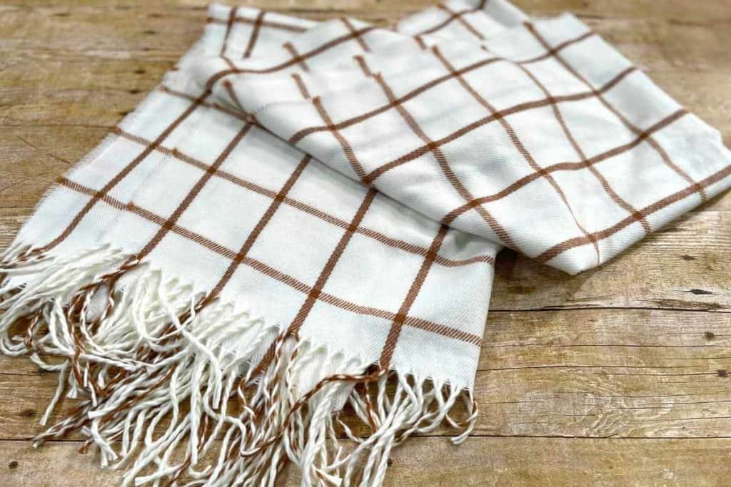 A large cream and brown plaid scarf with fringe on a wooden table