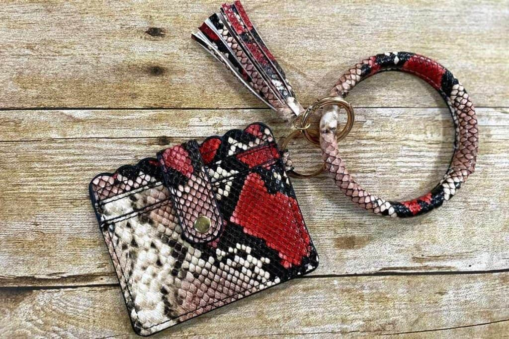 A feaux red and brown snakeskin bangle bracelet that connects to a small wallet/id holder